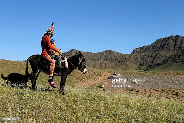 Kazak sheperd waves to Toyota team Yong Zhou and copilot Xavier Panseri as they take part in the Silk Way rally near the Bartogai lake near Almaty in...
