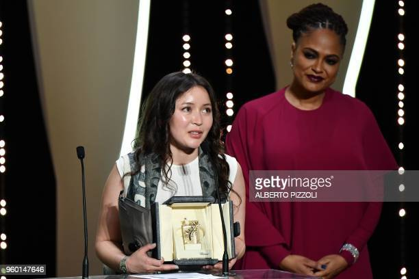Kazakh actress Samal Yeslyamova delivers a speech on stage next to US director and screenwriter and member of the Feature Film Jury Ava DuVernay...