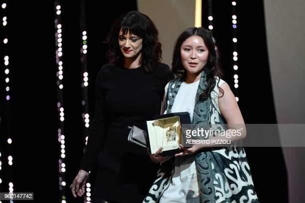 Kazakh actress Samal Yeslyamova leaves the stage with Italian actress Asia Argento after she was awarded with the Best Actress Prize for her part in...