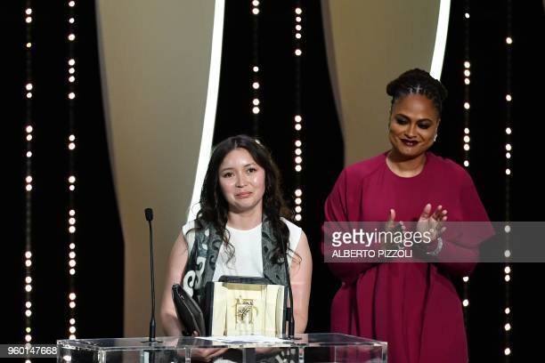 Kazakh actress Samal Yeslyamova stands on stage next to US director and screenwriter and member of the Feature Film Jury Ava DuVernay after she was...