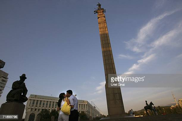 A Kazakh couple kiss at the base of the statue of Golden Sakovia erected in 1996 to celebrate 5 years of independence August 8 2006 in Almaty in the...