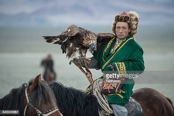 kazakh eagle hunter with his golden eagle on horseback - indigenes volk stock-fotos und bilder