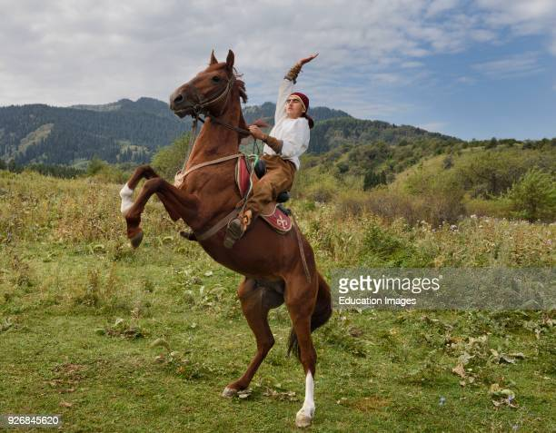 Kazakh horse rider with raised arm on rearing gelding in Huns village Kazakhstan