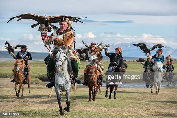 kazakh mongolian cavalry golden eagle hunter across the river in altai mountains - independent mongolia stock pictures, royalty-free photos & images