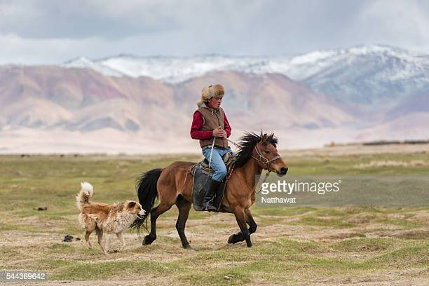 Kazakh Nomad Riding Horse with His Dog