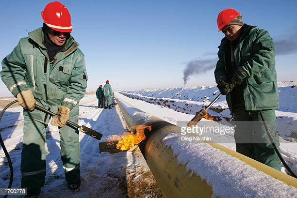 Kazakh oil workers lay an oil pipeline by the Canadian oil company Hurricane Kumkol Munai December 19 2002 about 200 km north of Kyzylorda Kazakhstan...