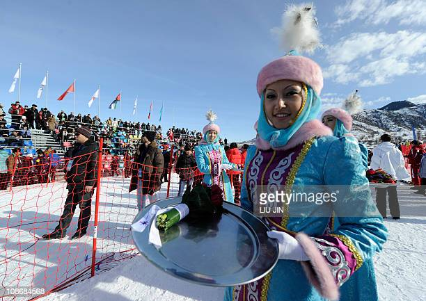 A Kazakh podium assistant waits for an awarding ceremony for men's and women's freestyle skiing aerials event of the 7th Asian Winter Games at the...