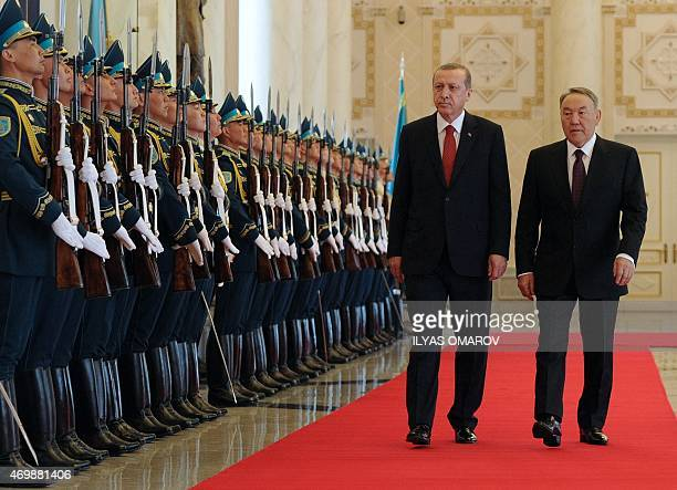 Kazakh President Nursultan Nazarbayev and his Turkish counterpart Recep Tayyip Erdogan review an honor guard during a welcoming ceremony in Astana on...