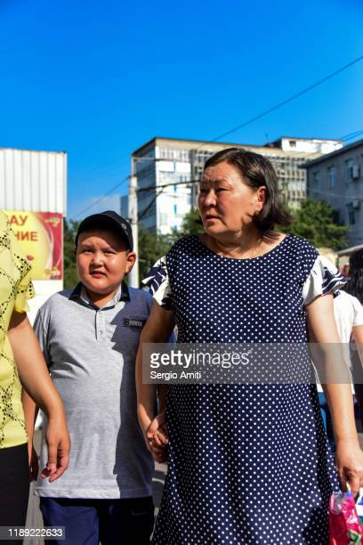 kazakh woman and boy walking at market in almaty - sergio amiti stock pictures, royalty-free photos & images