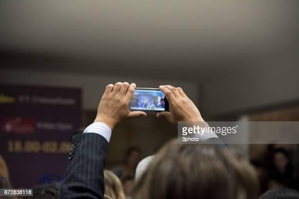 Kazakhstan - Man doing photo shooting via smartphone at the event