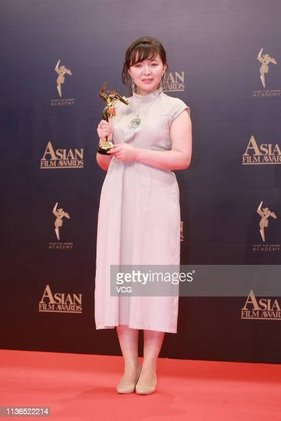 Kazakhstan's actress Samal Yeslyamova poses with the trophy backstage after winning the Best Actress during the 13th Asian Film Awards on March 17...