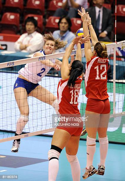 Kazakhstan's attacker Tatyana Ryurova spikes the ball against Puerto Rican blockers Ania Ruiz and Jetzabel del Valle during a match of the final...