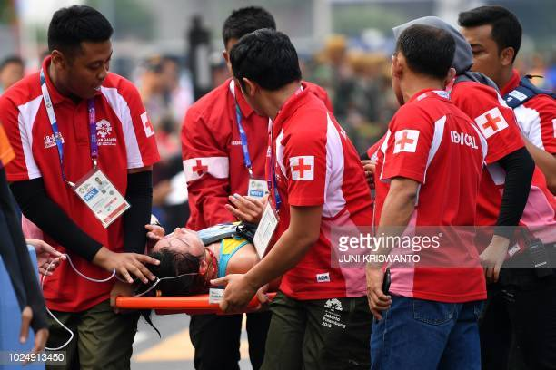Kazakhstan's Ayman Ratova is given medical assistance after collapsing after finishing the women's 20km walk race competition during the 2018 Asian...