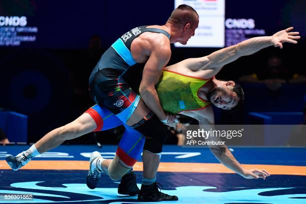 Kazakhstan's Demeu Zhadrayev competes with Germany's Frank Staebler during the men's GrecoRoman Seniors 71kg category final bout of the FILA World...