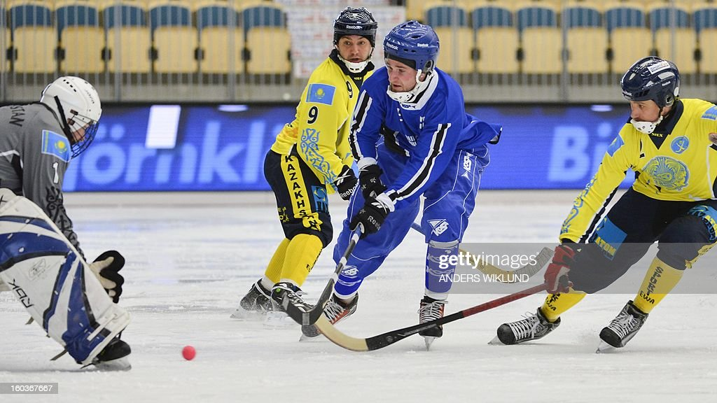 Kazakhstan's goalkeeper Alexander Kossynchuk tries to catch the ball played by Finland's Tomi Hauska (C) during the Bandy World Championship match Finland vs Kazakhstan in Vanersborg January 30, 2013.