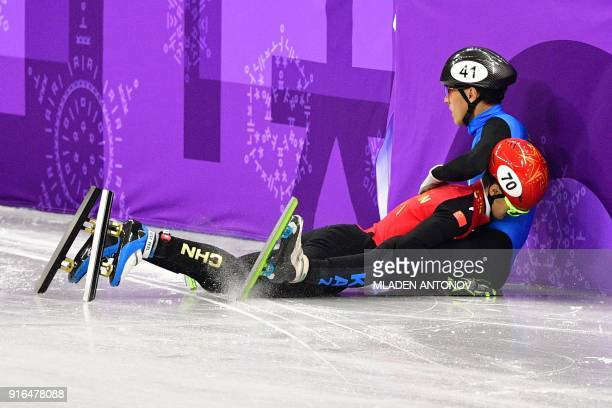 Kazakhstan's Nurbergen Zhumagaziyev and China's Xu Hongzhi crash in the men's 1,500m short track speed skating heat event during the Pyeongchang 2018...