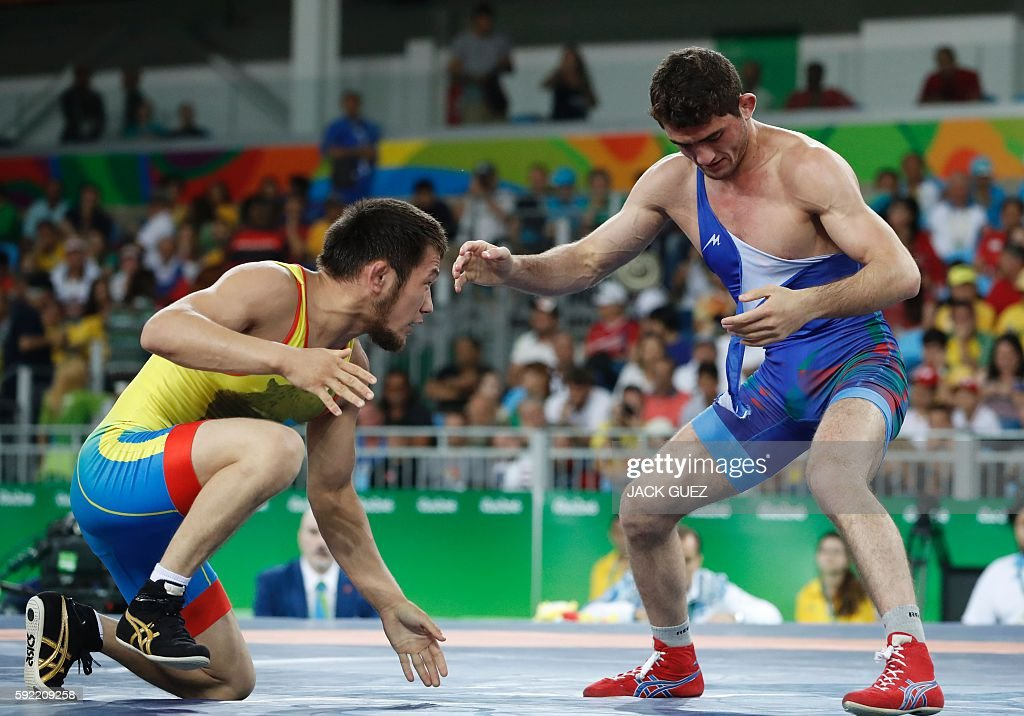TOPSHOT - Kazakhstan's Nurislam Sanayev (red) wrestles with Azerbaijan's Haji Aliyev in their men's 57kg freestyle repechage round 2 match on August 19, 2016, during the wrestling event of the Rio 2016 Olympic Games at the Carioca Arena 2 in Rio de Janeiro. / AFP / Jack GUEZ