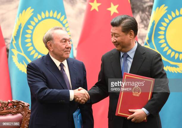 Kazakhstan's President Nursultan Nazarbayev shakes hands with Chinese President Xi Jinping during a signing ceremony in the Great Hall of the People...