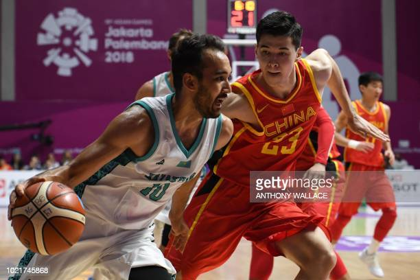 Kazakhstan's Rustam Murzagaliyev tries to get past China's Abudushalamu Abudurexiti during the men's preliminary round Group D basketball match...