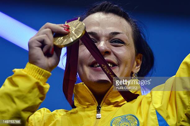 Kazakhstan's Svetlana Podobedova poses on the podium with her gold medal after the women's 75kg group A weightlifting event of the London 2012...