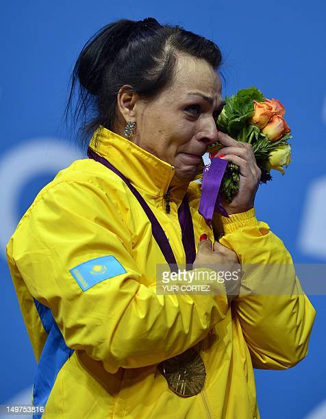 Kazakhstan's Svetlana Podobedova wipes a tear on the podium with her gold medal after the women's 75kg group A weightlifting event of the London 2012...