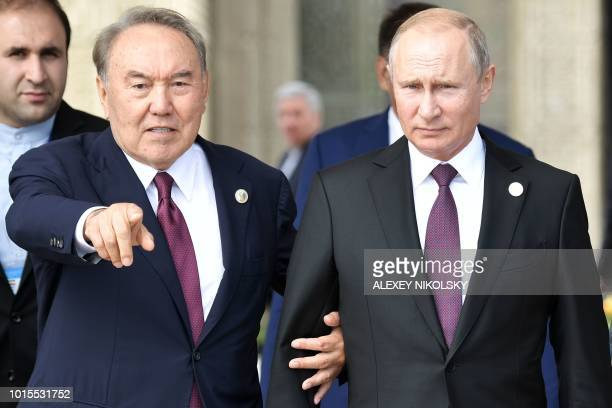 Kazakhtan's President Nursultan Nazarbayev and Russian President Vladimir Putin react during their walking on Caspian sea embankment at the 5th...