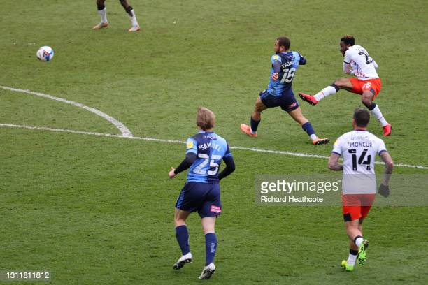 Kazenga LuaLua of Luton Town scores their team's second goal under pressure from Curtis Thompson of Wycombe Wanderers during the Sky Bet Championship...