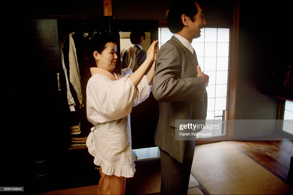 Housewife Helping Husband Prepare for Work : News Photo
