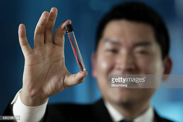 Kazuhide Sekiyama president and chief executive officer of Spiber Inc holds a tube containing synthetic spider silk for a photograph in Tokyo Japan...