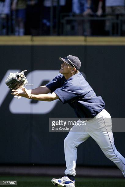 Kazuhiro Sasaki of the Seattle Mariners catches his glove after he tossed it in the air trying to catch a home run ball during batting practice prior...