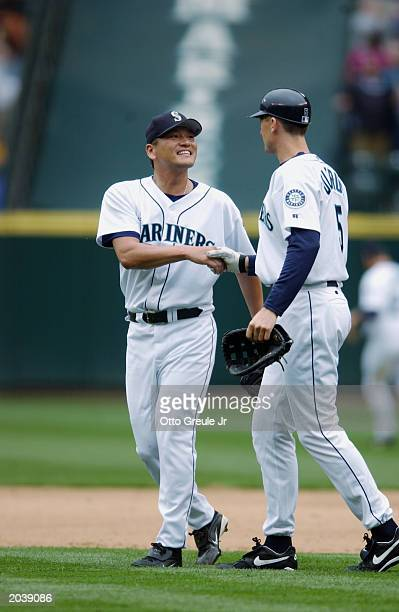 Kazuhiro Sasaki of the Seattle Mariners is congratulated by teammate John Olerud following the game against the Kansas City Royals at Safeco Field on...