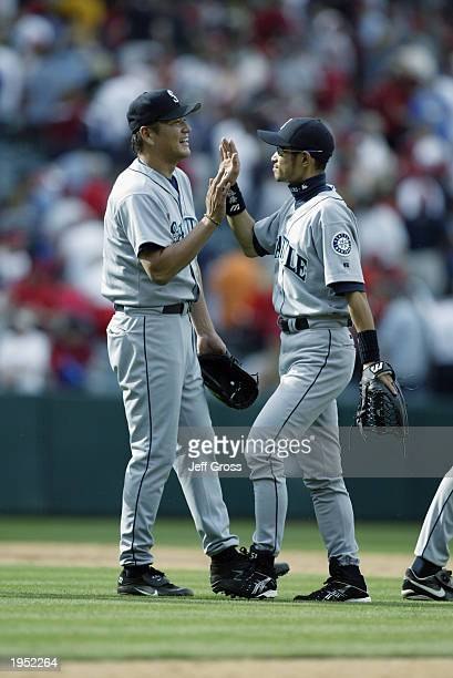 Kazuhiro Sasaki of the Seattle Mariners receives a high five from teammate Ichiro Suzuki after Sasaki saved the game against Anaheim Angels on April...