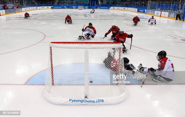 Kazuhiro Takahashi of Japan scores a goal over Kjell Hamar goaltender of Norway in the Ice Hockey Classification game between Norway and Japan during...