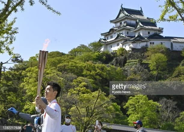 Kazuhito Tanaka, a silver medalist in the men's gymnastics team event at the 2012 London Olympics, runs during the Tokyo Olympic torch relay in...