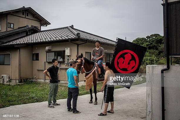 Kazuhzko Suzuki, 53 is given instructions by senior samurai Yoshikatsu Mottate during practice before participating in his first Soma Nomaoi festival...