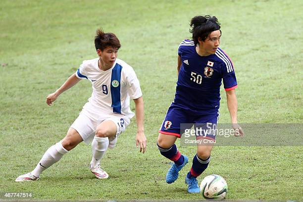 Kazuki Anzai of Japan battles with Leong Tak Wai of Macau during the AFC U23 Championship Qualifier Group I match between Japan and Macau at Shah...