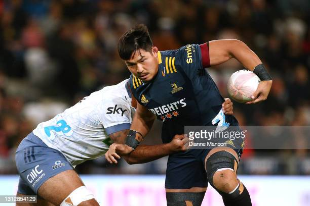 Kazuki Himeno of the Highlanders is tackled by Akira Ioane of the Blues during the round eight Super Rugby Aotearoa match between the Highlanders and...