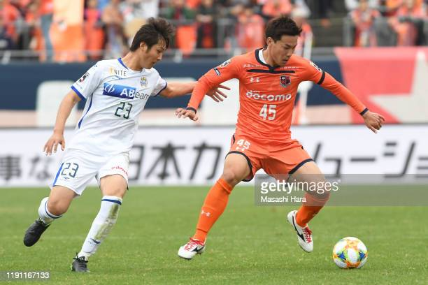 Kazuki Kushibiki of Omiya Ardija and Yuta Kumamoto of Montedio Yamagata compete for the ball during the J.League J1/J2 Play-Off first round match...