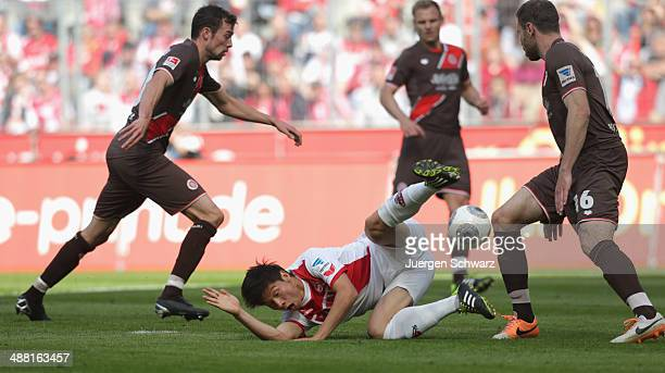 Kazuki Nagasawa of Cologne falls in front of Markus Thorandt of Hamburg during the Second Bundesliga match between 1 FC Koeln and FC St Pauli at...