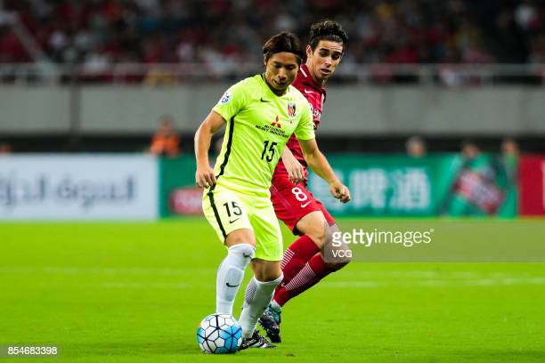 Kazuki Nagasawa of Urawa Red Diamonds and Oscar of of Shanghai SIPG compete for the ball during 2017 AFC Champions League semifinal first leg match...