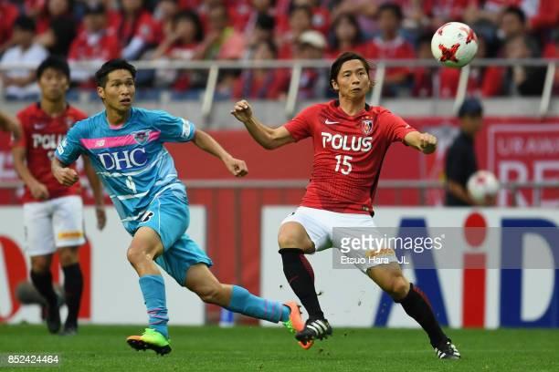 Kazuki Nagasawa of Urawa Red Diamonds and Riki Harakawa of Sagan Tosu compete for the ball during the JLeague J1 match between Urawa Red Diamonds and...
