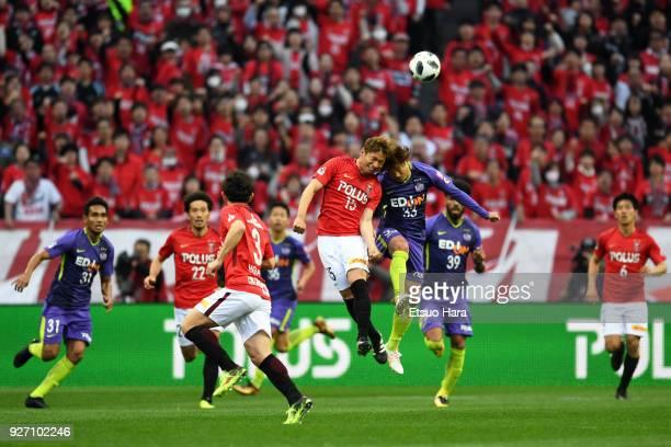 Kazuki Nagasawa of Urawa Red Diamonds and Takuya Wada of Sanfrecce Hiroshima compete for the ball during the JLeague J1 match between Urawa Red...