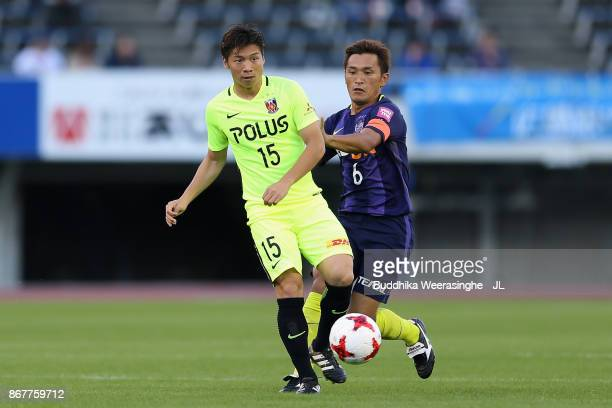 Kazuki Nagasawa of Urawa Red Diamonds and Toshihiro Aoyama of Sanfrecce Hiroshima compete for the ball during the JLeague J1 match between Sanfrecce...