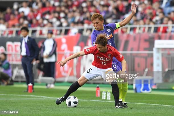 Kazuki Nagasawa of Urawa Red Diamonds and Toshihiro Aoyama of Sanfrecce Hiroshima compete for the ball during the JLeague J1 match between Urawa Red...