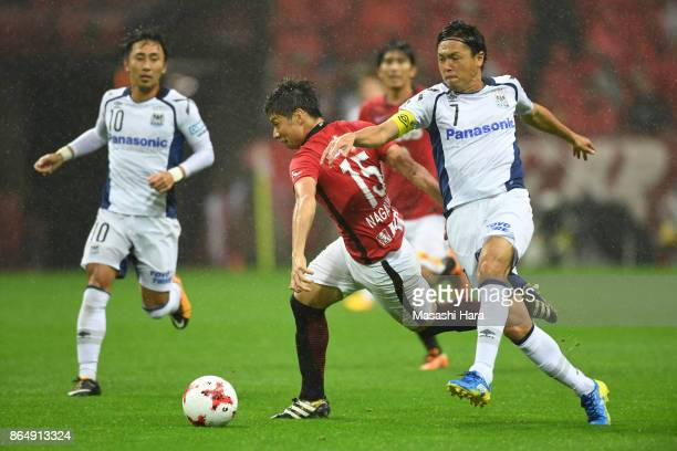 Kazuki Nagasawa of Urawa Red Diamonds and Yasuhito Endo of Gamba Osaka compete for the ball during the JLeague J1 match between Urawa Red Diamonds...