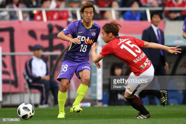 Kazuki Nagasawa of Urawa Red Diamonds and Yoshifumi Kashiwa of Sanfrecce Hiroshima compete for the ball during the JLeague J1 match between Urawa Red...