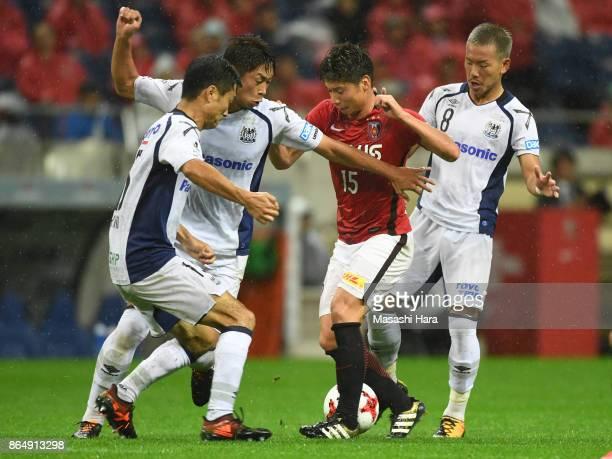 Kazuki Nagasawa of Urawa Red Diamonds and Yosuke Ideguchi Genta Miura and Yasuyuki Konno of Gamba Osaka compete for the ball during the JLeague J1...