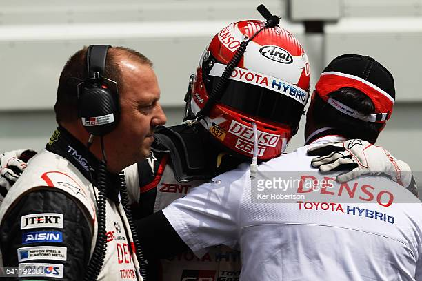 Kazuki Nakajima of Toyota Gazoo Racing is helped back to his garage by team mates after suffering engine problems while leading at the end of the Le...