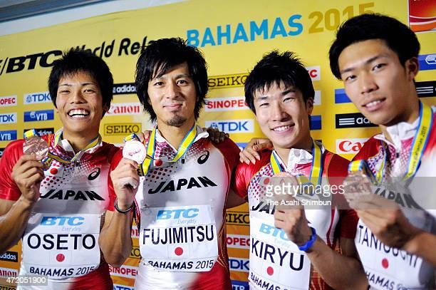 Kazuma Oseto, Kenji Fujimitsu, Yoshihide Kiryu and Kotaro Taniguchi pose for photographs after winning bronze medals in the final of the men's 4 x...