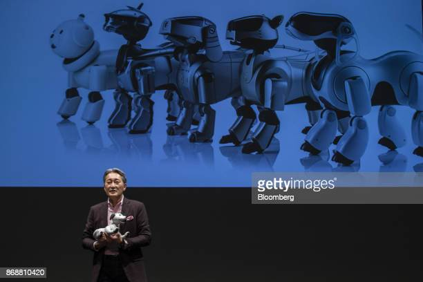 Kazuo Hirai president and chief executive officer of Sony Corp speaks while holding one of the the company's new robotic dogs which the company is...